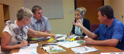 : Regional committee members discuss new bike trail guides geared to visitors.   l-r, Colleen Pennington, EcDev officer for Penticton; John Powell, EcDev officer for Okanagan Falls; Raquel Miriam and Chris Bower from Tourism Penticton.